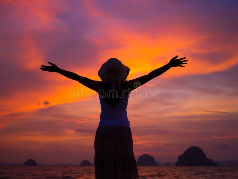 Silueta del sombrero que lleva de la mujer con los brazos abiertos bajo salida del sol cerca del mar imagenes de archivo