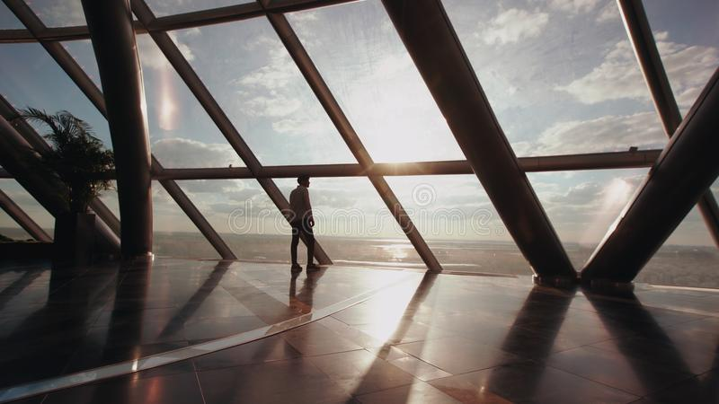 Silueta del soporte del hombre de negocios cerca de la ventana en el edificio de oficinas moderno foto de archivo libre de regalías