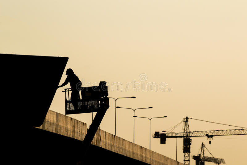 Silueta del trabajador de construcción en el andamio en el construc fotografía de archivo