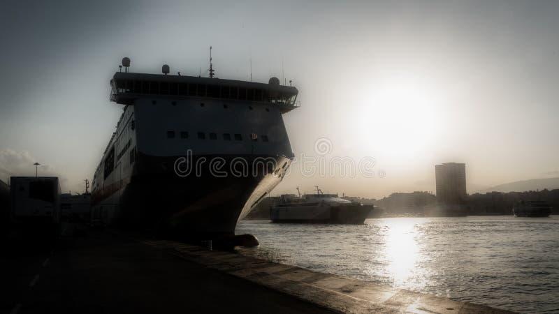 Silueta del transbordador griego en el muelle en el puerto de Pireaus imagenes de archivo