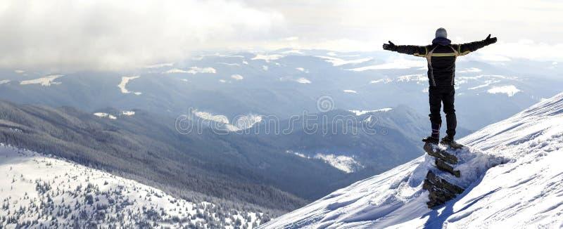 Silueta del turista solo que se coloca en el top nevoso de la montaña en los wi foto de archivo libre de regalías