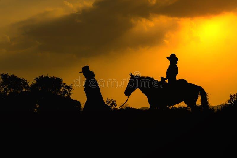 Silueta del vaquero en caballo durante puesta del sol agradable fotografía de archivo libre de regalías