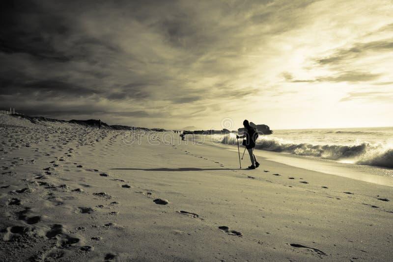 Silueta del viajero del trekker que camina en la playa arenosa con día soleado caliente de las ondas en octubre en costa atlántic imagen de archivo