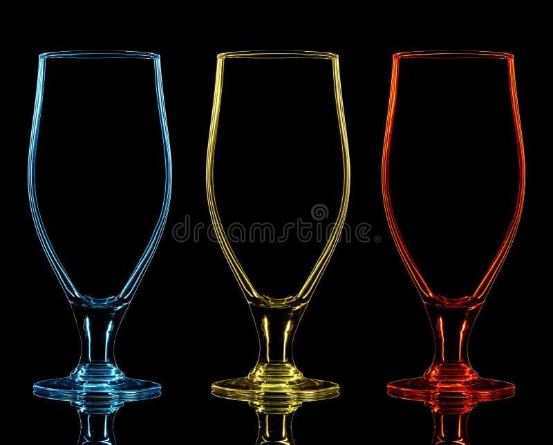 Silueta del vidrio de cerveza del color en fondo negro imagenes de archivo
