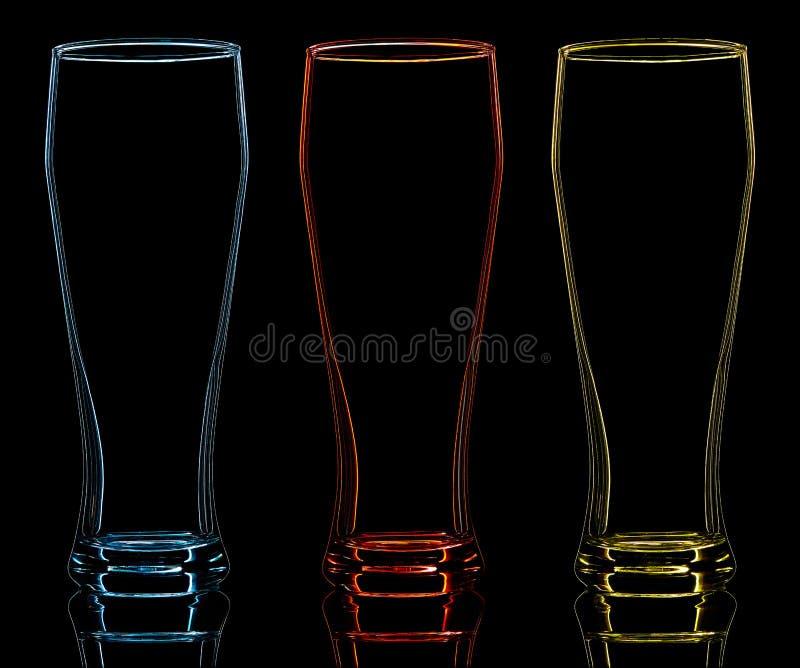 Silueta del vidrio de cerveza del color en fondo negro fotografía de archivo