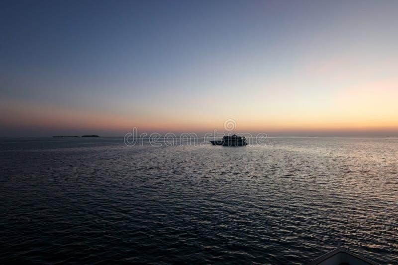 Silueta del yate grande en el océano en puesta del sol rosada con la isla en fondo fotografía de archivo libre de regalías