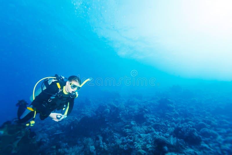 Silueta del zambullidor de equipo de submarinismo cerca de la parte inferior de mar imágenes de archivo libres de regalías