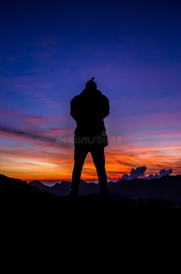 Silueta delante de una puesta del sol hermosa foto de archivo libre de regalías