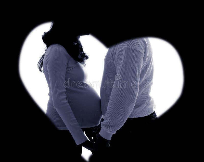 Silueta embarazada de los pares en oscuro fotografía de archivo libre de regalías