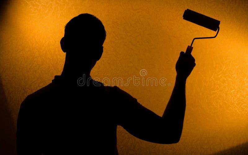 Silueta encendida parte posterior del hombre con el pintura-rodillo imagen de archivo libre de regalías
