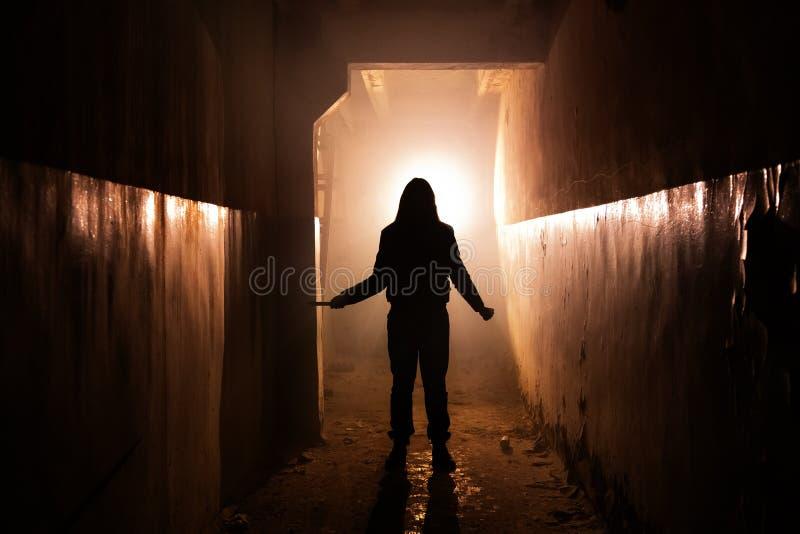 Silueta espeluznante del hombre desconocido con el cuchillo en el edificio abandonado oscuro Horror sobre concepto maniaco foto de archivo libre de regalías