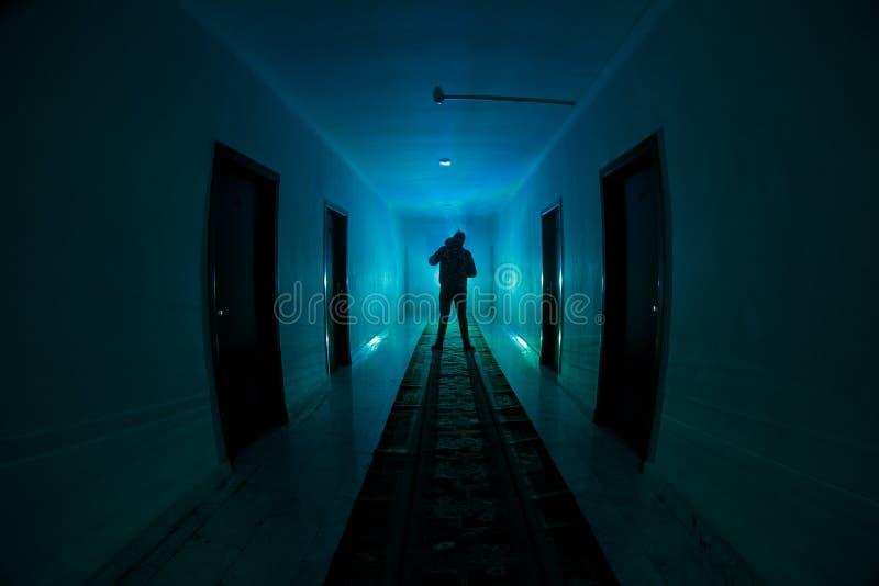 Silueta espeluznante en el edificio abandonado oscuridad Pasillo oscuro con las puertas de gabinete y luces con la silueta del ho fotografía de archivo