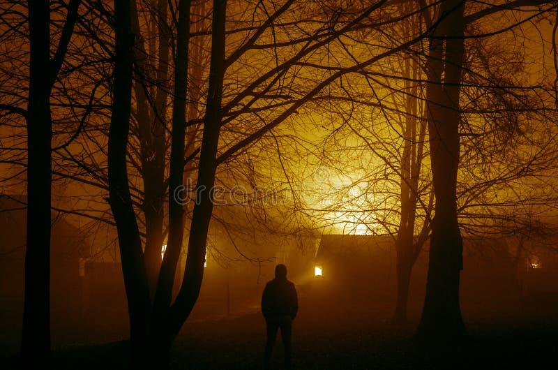 silueta extraña en un bosque fantasmagórico oscuro en la noche, luces surrealistas con el hombre espeluznante, burning del paisaj imagen de archivo libre de regalías