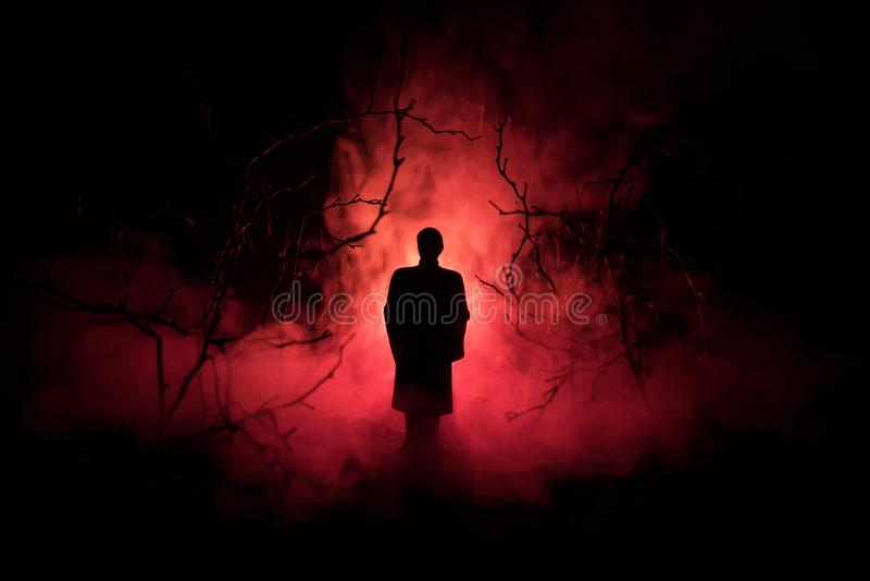 Silueta extraña en un bosque fantasmagórico oscuro en la noche, luces surrealistas del paisaje místico con el hombre espeluznante fotografía de archivo