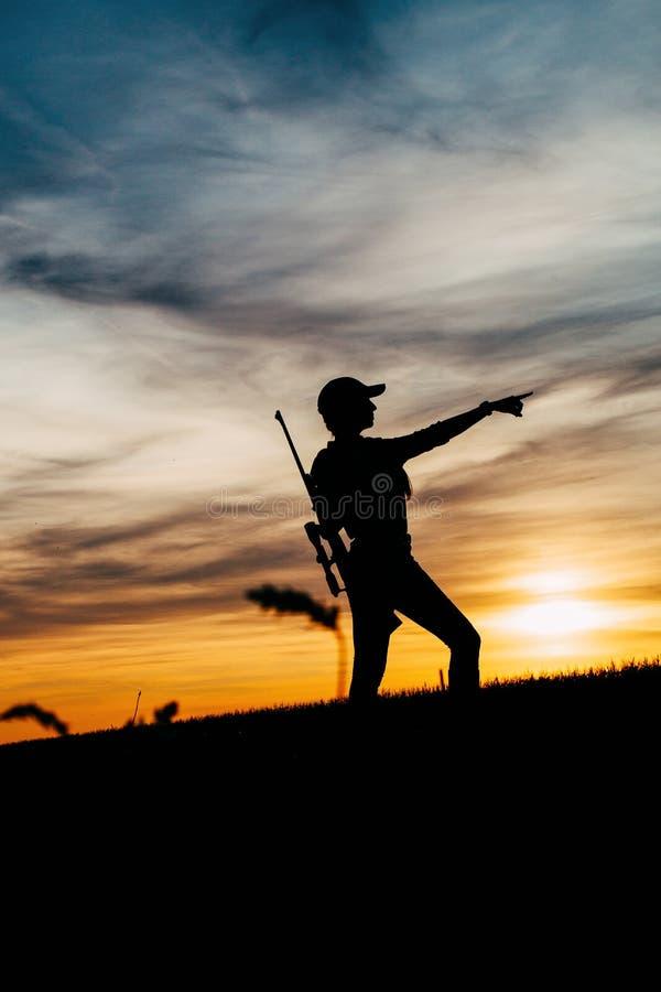 Silueta femenina del cazador en puesta del sol imagen de archivo