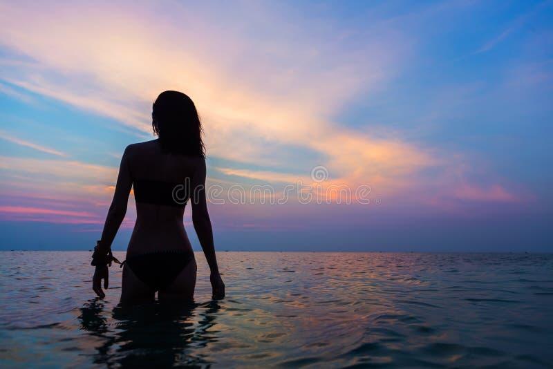 Silueta femenina hermosa en el mar de la tarde imágenes de archivo libres de regalías