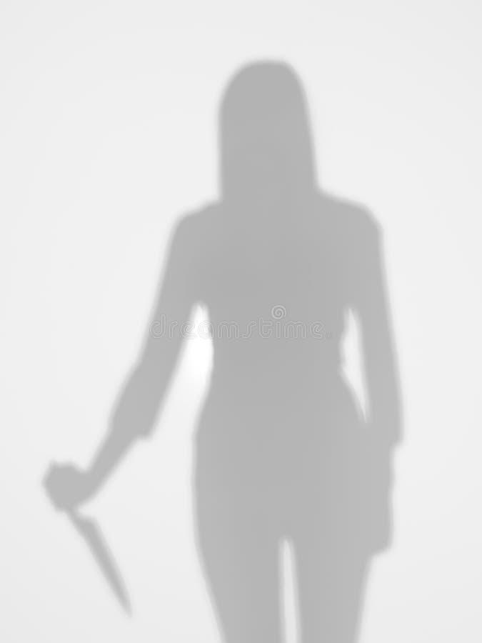 Silueta femenina que sostiene un cuchillo detrás de la superficie difusa fotos de archivo libres de regalías