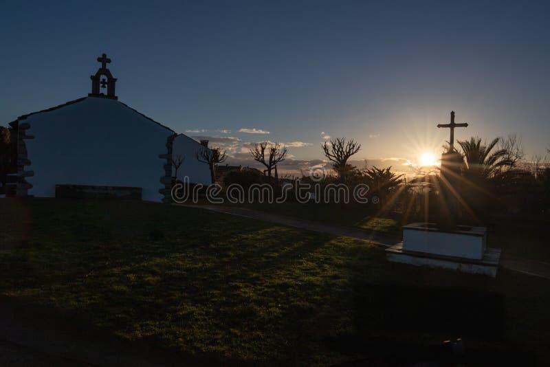 Silueta hermosa de la capilla y de la cruz en salida del sol en la costa de Atlántico en el bidart, país basque imagenes de archivo