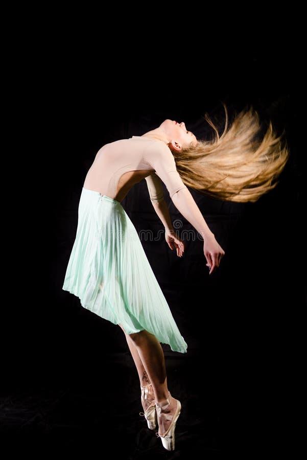 Silueta hermosa del baile de la señora joven en fondo negro del copyspace imagenes de archivo