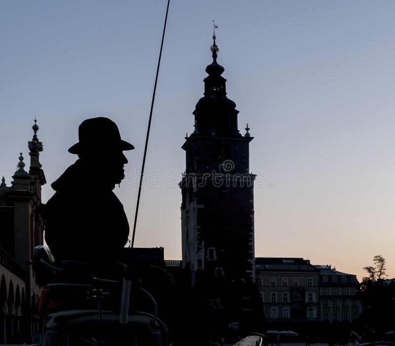 Silueta hermosa del cochero traído por caballo del carro con en el fondo la ciudad vieja de Kraków, Polonia fotos de archivo libres de regalías