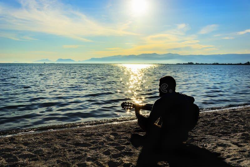 Silueta Hombres jovenes que tocan la guitarra mientras que se sienta en la playa fotografía de archivo