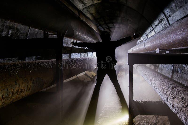 Silueta humana con en la comunicación subterráneo, la calefacción principal, el túnel de la alcantarilla, el etc foto de archivo libre de regalías