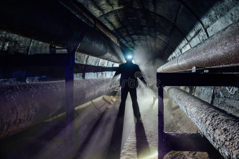 Silueta humana con la linterna llevada en la comunicación subterráneo, la calefacción principal, el túnel de la alcantarilla, el  imágenes de archivo libres de regalías