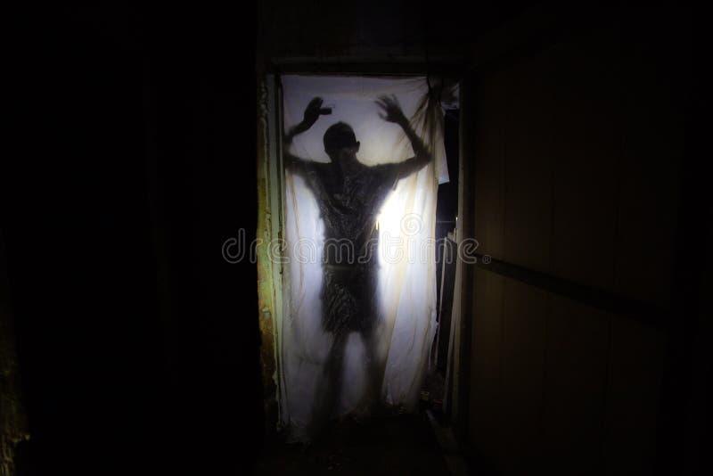 Silueta humana detrás de la película del embalaje en sitio espeluznante oscuro del edificio abandonado fotos de archivo
