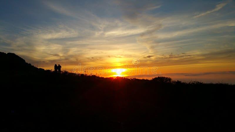 Silueta intrépida distante de la puesta del sol foto de archivo
