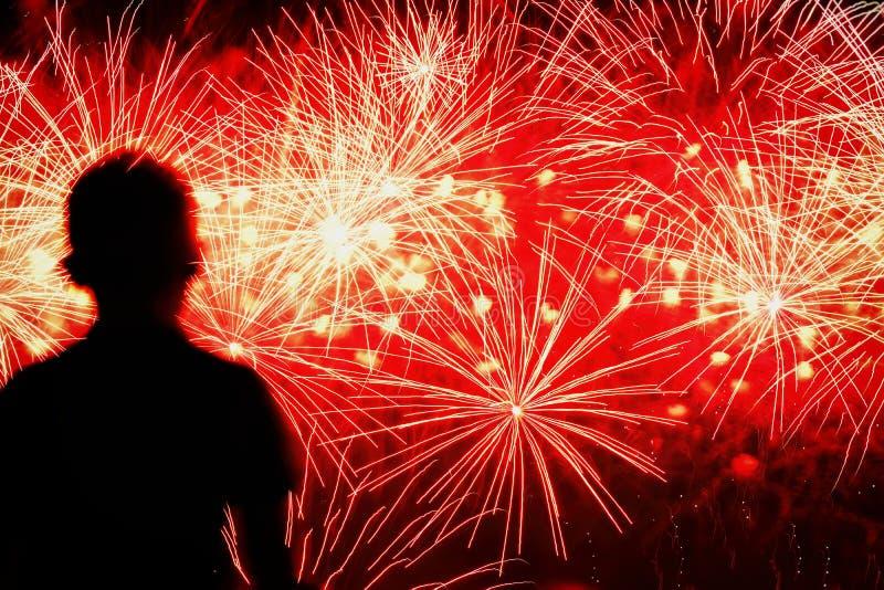 Silueta irreconocible de un niño con el suyo de nuevo a nosotros, que mira los fuegos artificiales espectaculares de la demostrac fotografía de archivo libre de regalías