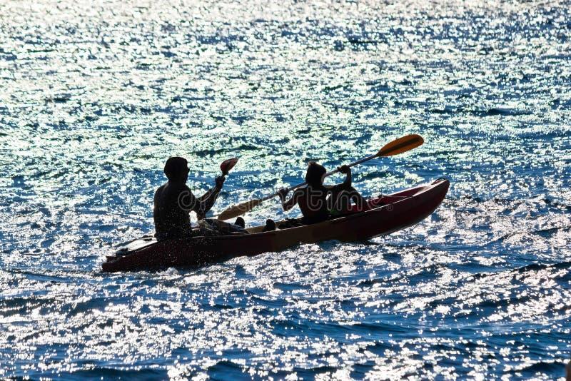 Silueta kayaking del padre y del hijo foto de archivo