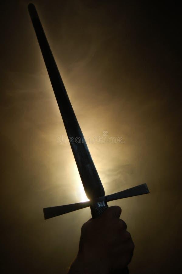 Silueta medieval de la espada en el backlighting fotografía de archivo