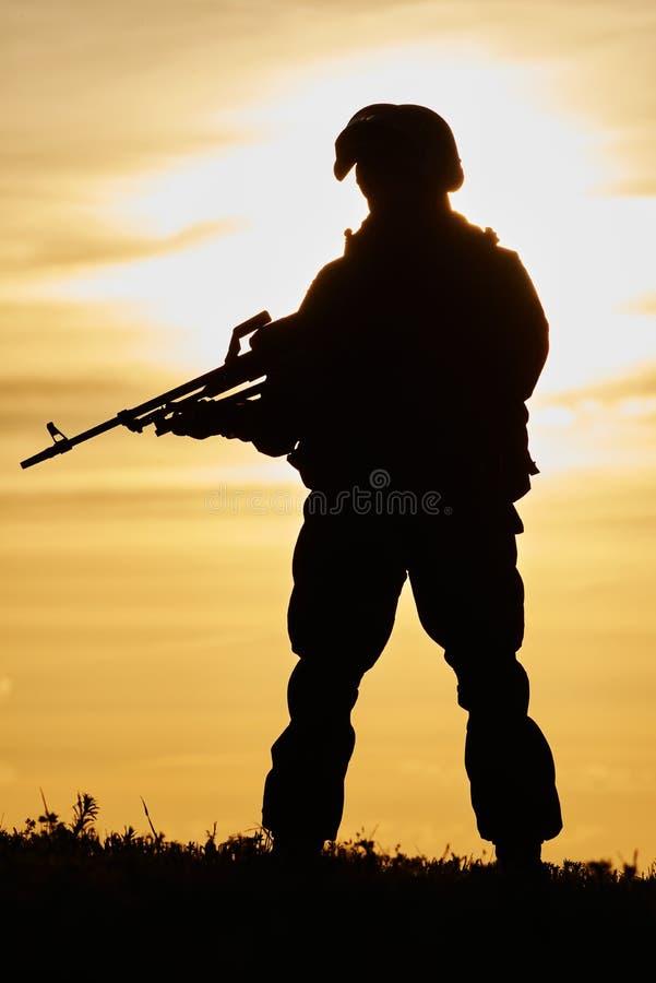 Silueta militar del soldado con la ametralladora foto de archivo