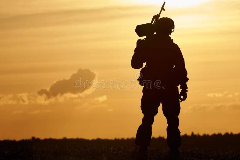 Silueta militar del soldado con la ametralladora fotografía de archivo libre de regalías