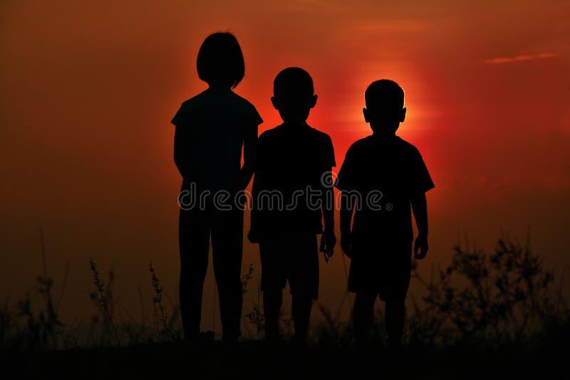 Silueta negra de tres ni?os que se unen Hay un cielo en la puesta del sol fotografía de archivo libre de regalías