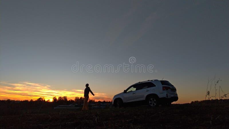 Silueta negra de una planta, de un hombre y de un coche en el fondo de una puesta del sol y de un cielo azul imagen de archivo libre de regalías