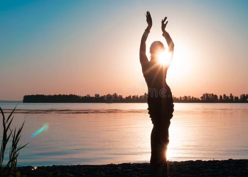Silueta oscura de bailar a la mujer delgada cerca del río grande foto de archivo libre de regalías