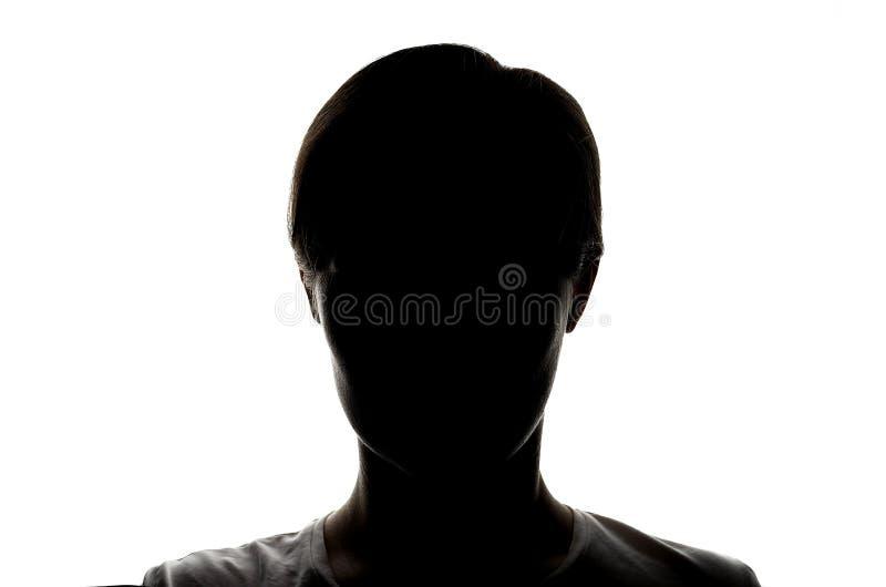 Silueta oscura de una chica joven en un fondo blanco, el concepto de anonimato foto de archivo libre de regalías