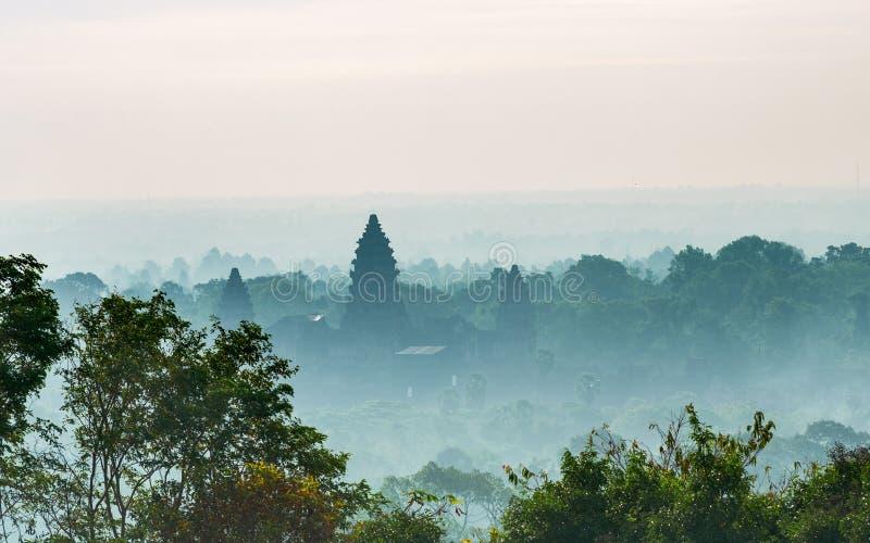 Silueta principal de la fachada del día soleado de Angkor Wat en medio del Telephoto verde brumoso del bosque de Phnom Bakheng Te fotografía de archivo libre de regalías