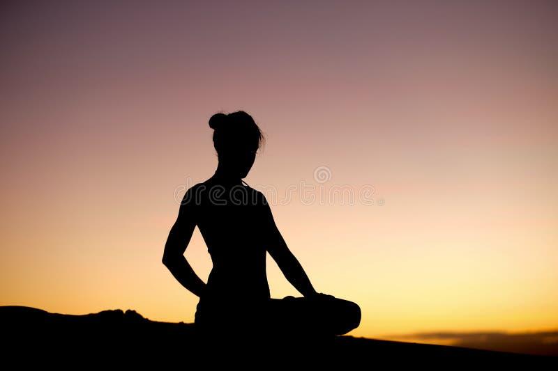 Silueta principal de la yogui en la playa imagen de archivo