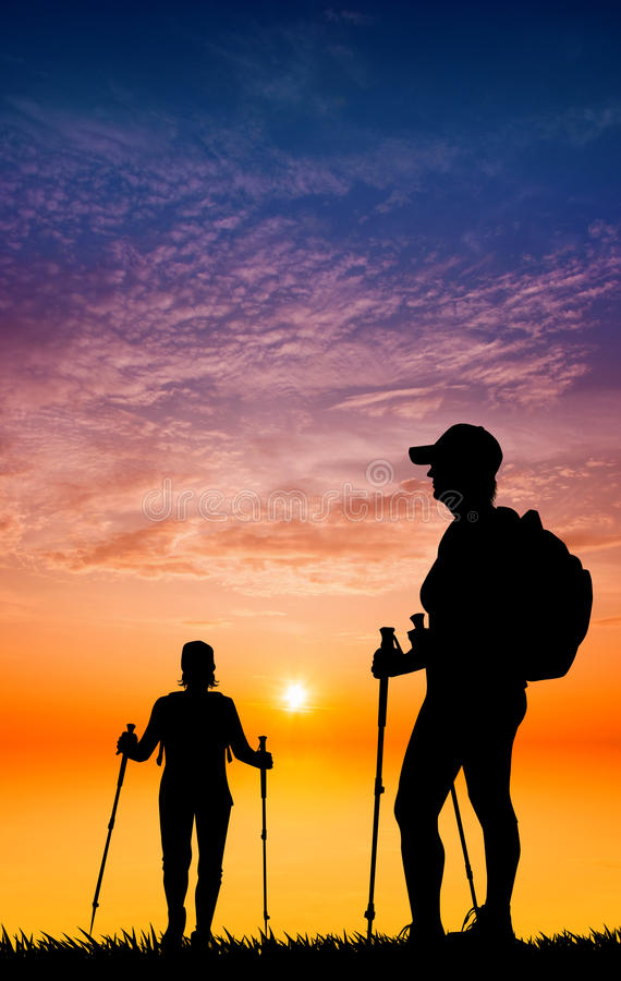 Silueta que camina nórdica en la puesta del sol ilustración del vector