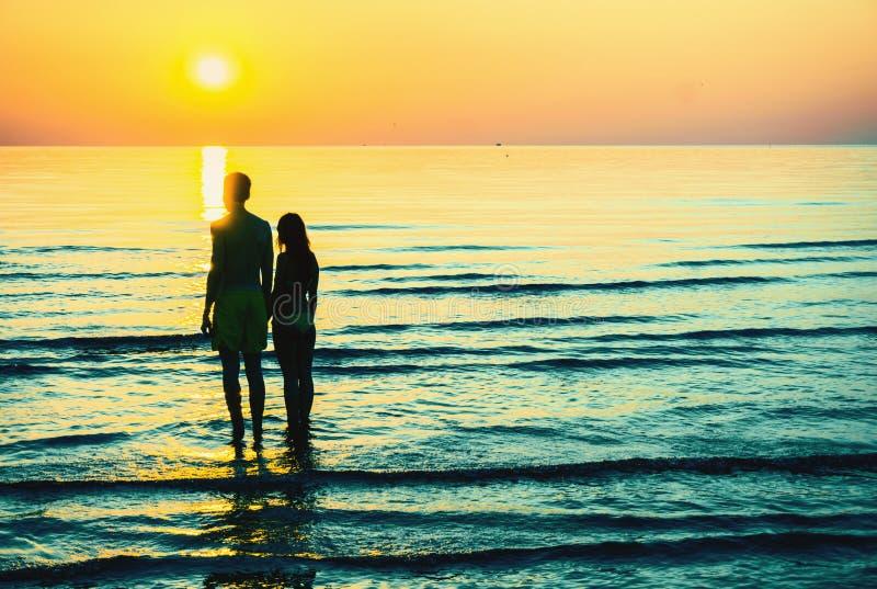 Silueta romántica de los pares en la puesta del sol en de la playa individuo y muchacha de común acuerdo en amor fotos de archivo libres de regalías
