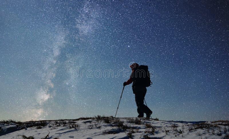 Silueta solitaria del caminante masculino adulto encima de la montaña coronada de nieve antes de amanecer Cielo estrellado en fo foto de archivo libre de regalías