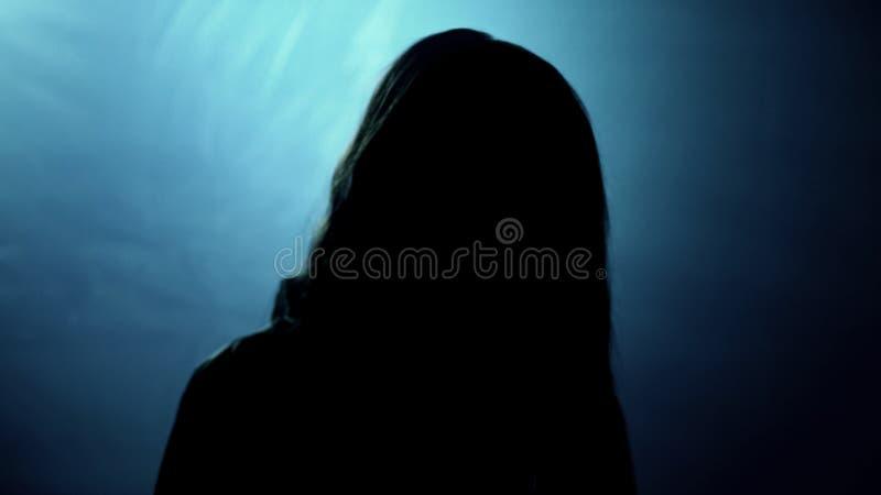 Silueta terrible de la mirada femenina en la cámara, víctima del asesino loco imágenes de archivo libres de regalías