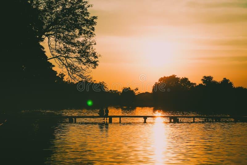 Silueta trasera de un par que se sienta en el puente que sostiene el lago hermoso del bosque de las manos en el fondo de la puest fotos de archivo libres de regalías
