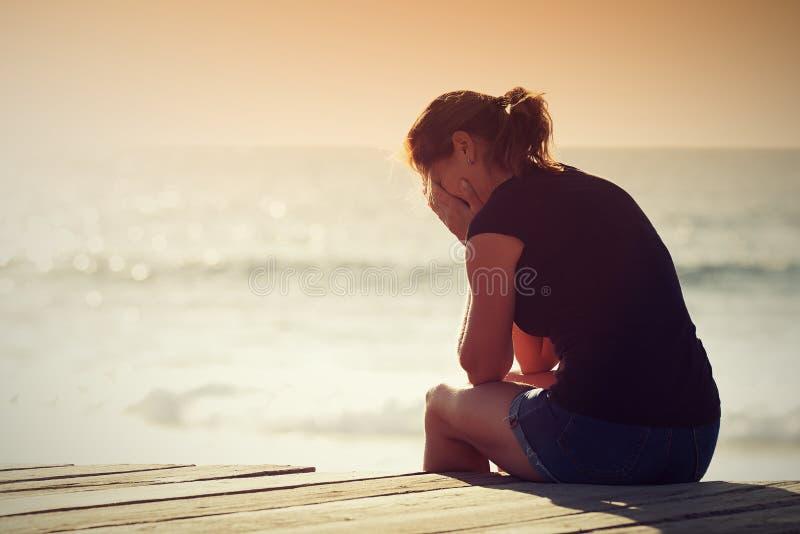 Silueta triste de la mujer preocupante en la playa imágenes de archivo libres de regalías