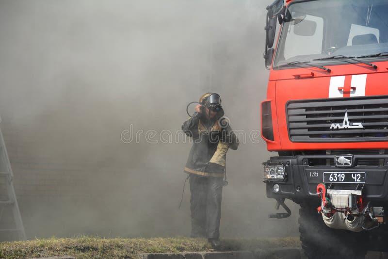 Silueta y firetruck del bombero en el humo imagenes de archivo