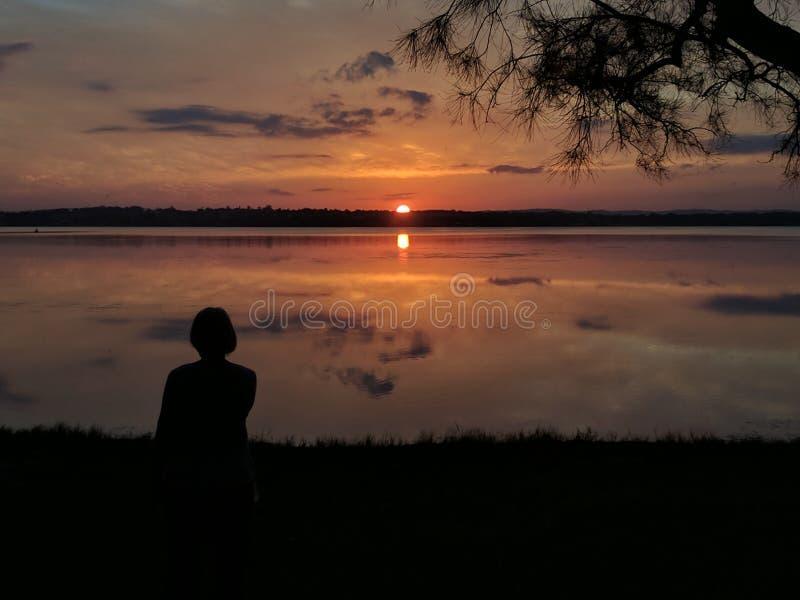 Silueta y puesta del sol imagenes de archivo