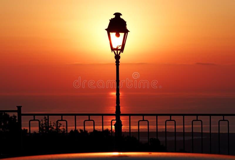Silueta y salida del sol del poste de la lámpara en costa mediterránea fotografía de archivo