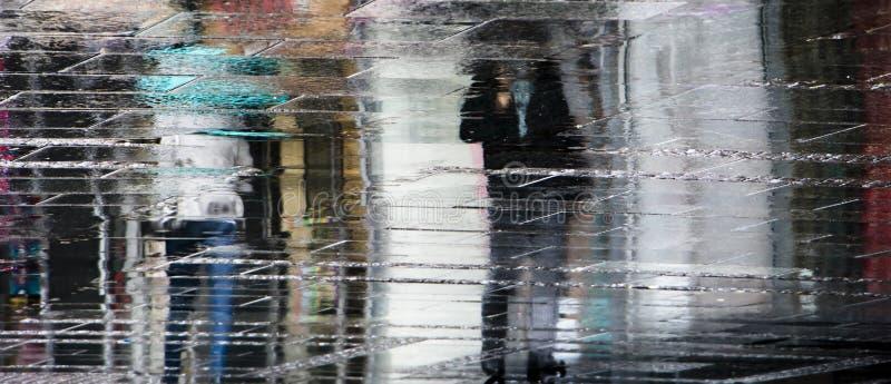 Siluetas borrosas de la sombra de la reflexión del peope que caminan solamente debajo del paraguas imagen de archivo